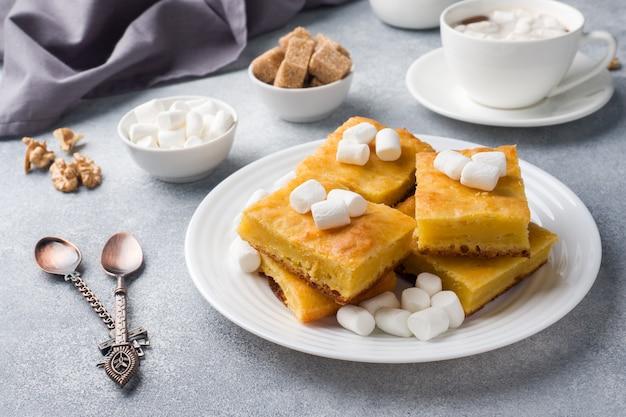 Кусочки вкусного тыквенного пирога с зефиром и орехами на тарелке