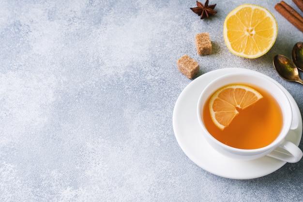 レモンとブラウンシュガー、シナモン、テーブルの上のアニスと紅茶のカップ。