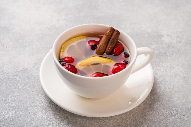 Напиток из ягод дикой розы с лимоном и медовой корицей. витаминный полезный отвар шиповника. копировать пространство
