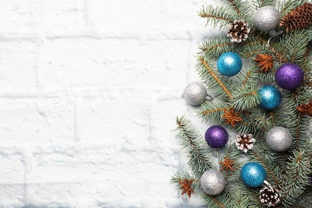 Рамка рождества сделанная из ели, украшений рождественской елки в серебре и сини на светлой предпосылке кирпича. копировать пространство квартира лежала.