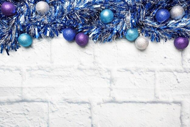 Рамка рождества сделанная из украшений сусали рождественской гирлянды в серебре и сини на светлой предпосылке кирпича. копировать пространство квартира лежала.