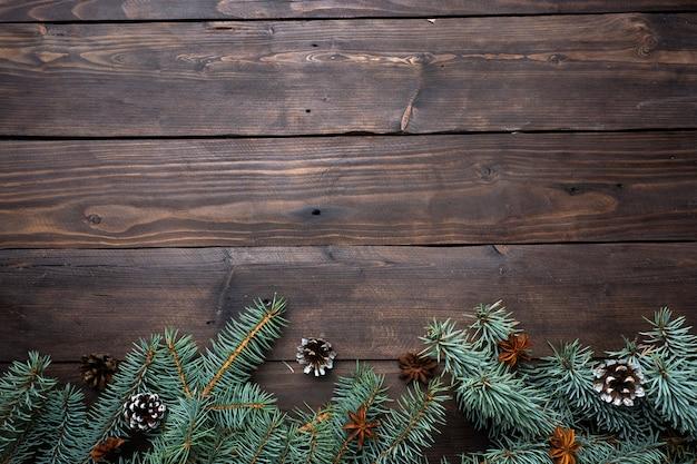 Рождественская елка с шишками на фоне темных деревянных. копировать пространство квартира лежала.