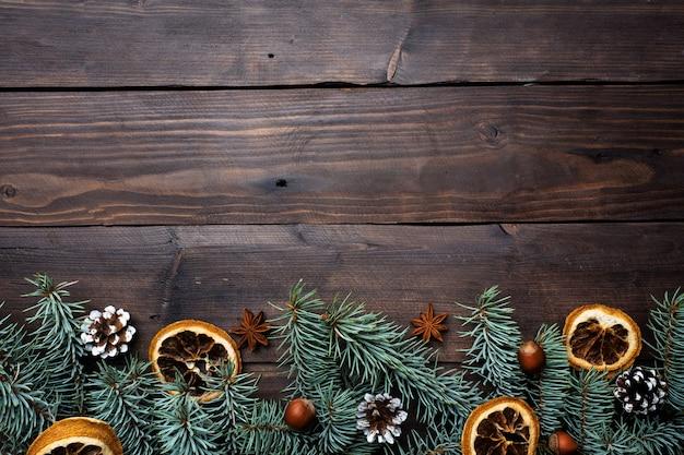 Рамка елей апельсинов конусов елки на фоне темных деревянных. копировать пространство квартира лежала.