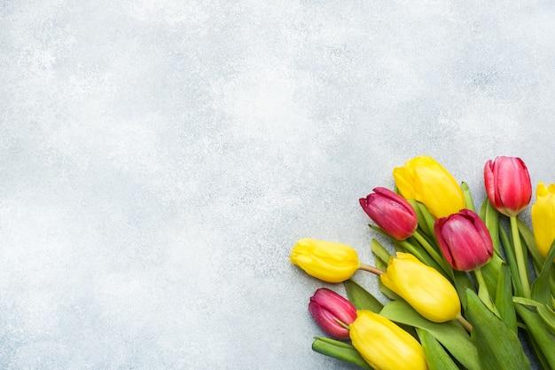 明るい青の背景に黄色とピンクのチューリップの花束。コピースペース