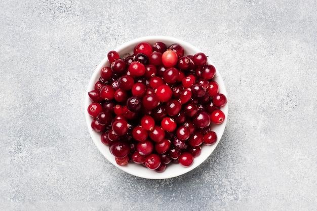 Свежие сырые ягоды клюквы в тарелку на сером фоне с копией пространства.