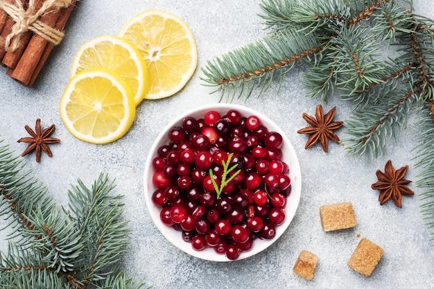 Свежие сырые ягоды клюквы и лимона в тарелке на сером фоне