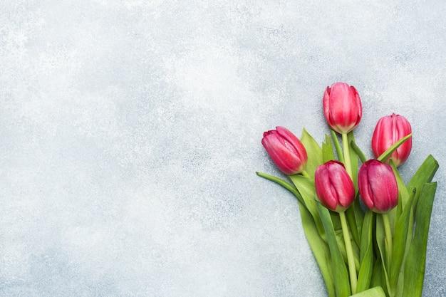明るい青の背景にピンクの深紅色のチューリップの花束。コピースペース