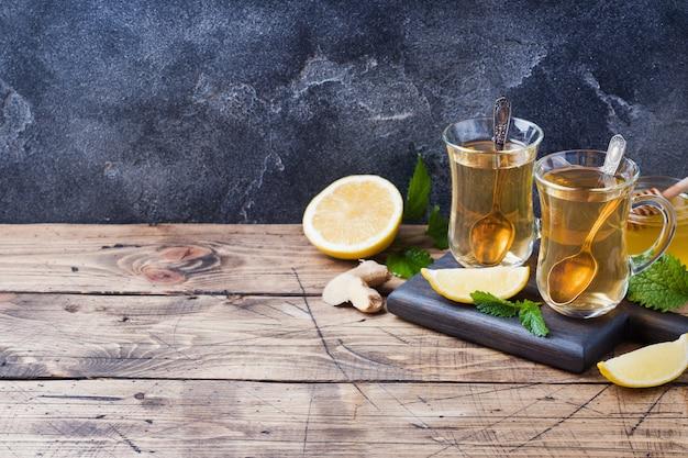 Две чашки натурального травяного чая, имбирь, лимон, мята и мед копирование пространства