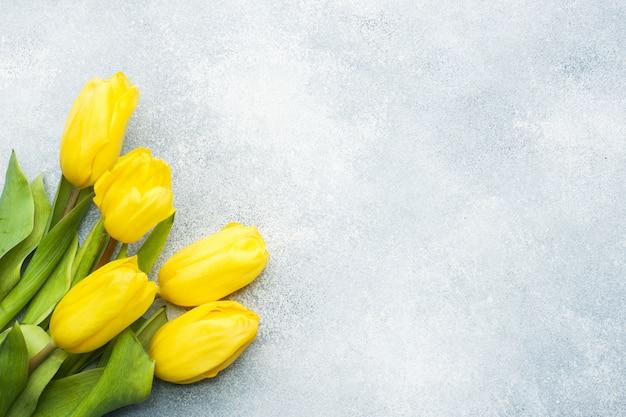 明るい青の背景に黄色のチューリップの花束。コピースペース