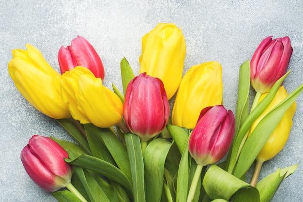 明るい青の背景に黄色とピンクのチューリップの花束。