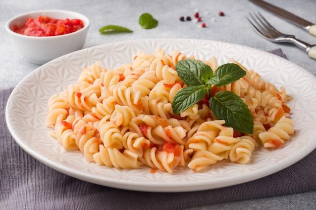 皿にチェリートマトとトマトソースを混ぜたスパイラルパスタ。