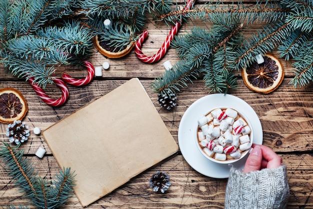 Чашка горячего шоколада с зефиром в руках мужчины в свитере. рождественская елка и украшения, тростниковая карамель и апельсины орехи деревянный фон копией пространства. новогодний подарок.