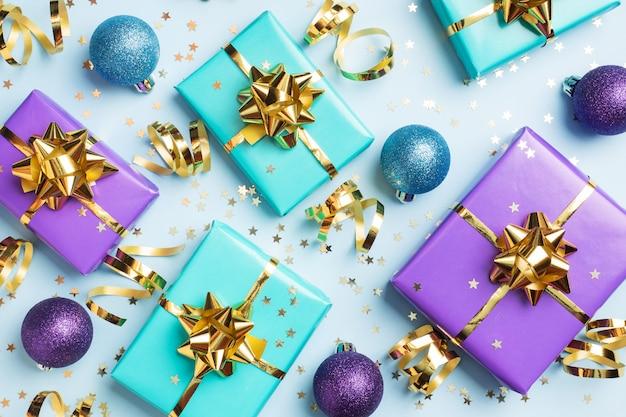 クリスマスと新年のお祝いのフラットレイアウト背景。ギフト用の箱は紫とターコイズで、青の背景に金リボンの弓と紙吹雪の星が付いています。上面図
