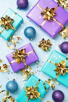 Квартира заложить фон для празднования рождества и нового года. подарочные коробки фиолетового и бирюзового цвета с золотыми лентами, бантами и конфетти на синем фоне. вид сверху