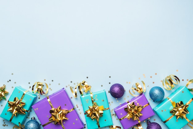 クリスマスと新年のお祝いのフラットレイアウト背景。ギフト用の箱は紫とターコイズで、青の背景に金リボンの弓と紙吹雪の星が付いています。トップビューコピースペース。