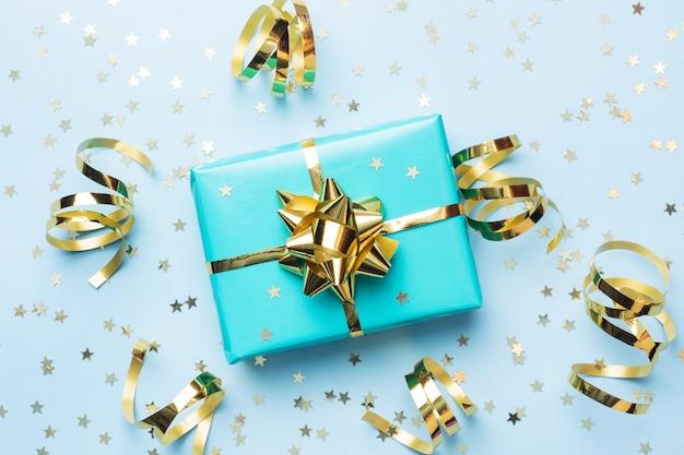 Квартира заложить фон для празднования рождества и нового года. подарочная коробка бирюзовый с золотыми лентами бантами и конфетти звезд на синем фоне. вид сверху копией пространства.
