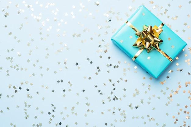 クリスマスと新年のお祝いのフラットレイアウト背景。ゴールドリボン弓と青色の背景に紙吹雪星とギフトボックスターコイズ。トップビューコピースペース。