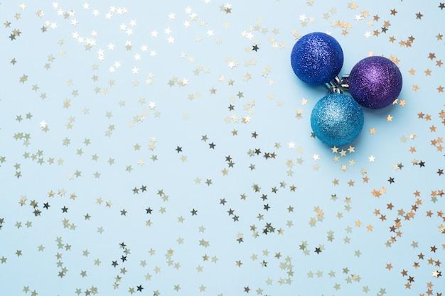 クリスマスと新年のお祝いのフラットレイアウト背景。ボールは紫とターコイズで、青の背景に金のリボンの弓と紙吹雪の星があります。トップビューコピースペース。