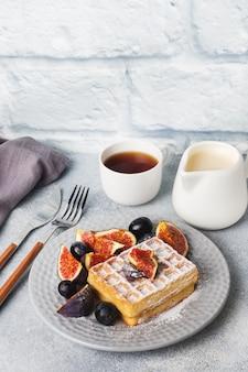 Традиционные бельгийские вафли с сахарной пудрой, виноградом и инжиром