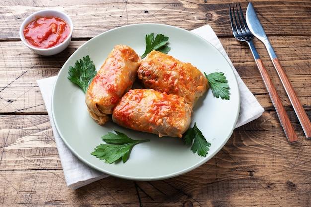 キャベツは牛肉、米、野菜を皿の上に巻きます。キャベツの葉と肉。木製の背景。