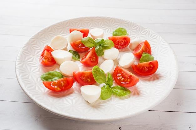 白いプレートにトマト、モッツァレラチーズ、バジルのカプレーゼサラダ。イタリア料理。