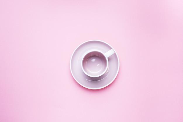 コピースペースとピンクの背景のテーブルの中央に受け皿と空のコーヒーカップ。上面図。ミニマリズム。