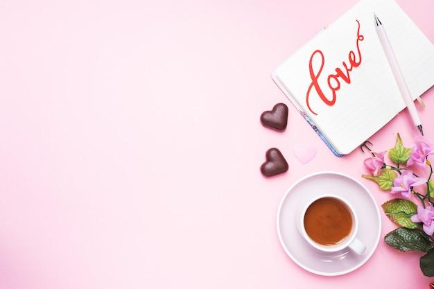 コンセプトバレンタインデー。チョコレート菓子とコーヒー、ピンクの背景の心。フラットレイアウトコピースペース。グリーティングカードとギフト。