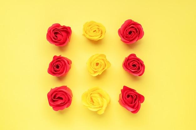 黄色の背景に赤と黄色のバラのつぼみ。バレンタインの日、結婚式のロマンスの概念。フラットレイアウトコピースペース。