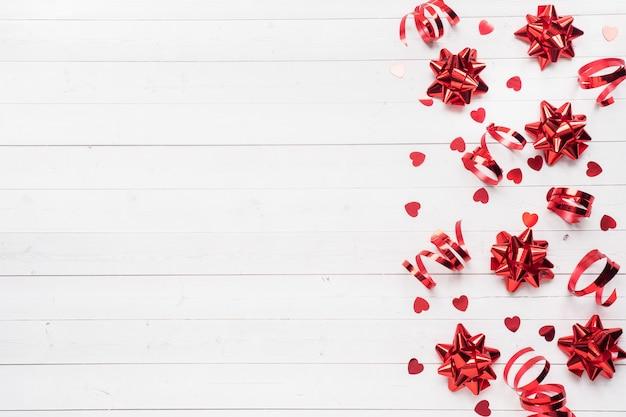 赤いリボンと弓、白地に紙吹雪の心。コピースペースフラットレイアウト。誕生日パーティー、バレンタインの結婚式のグリーティングカード。
