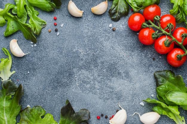 枝にチェリートマト新鮮なハーブとニンニクは暗い石のテーブルの上のスパイスでクローブします。