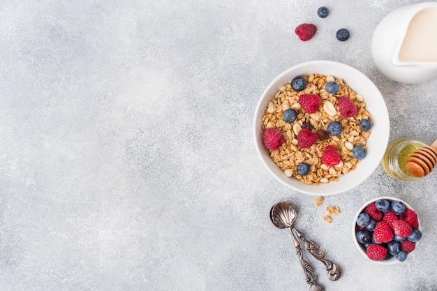健康的な朝食。新鮮なグラノーラ、ヨーグルトと灰色の背景に果実のミューズリー。コピースペース