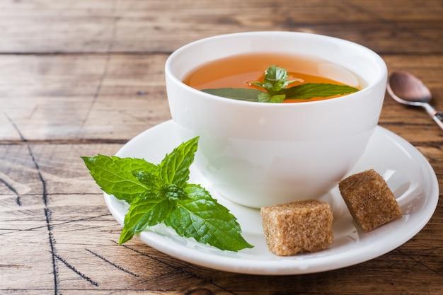 Чашка горячего чая с мятой и коричневым сахаром на деревянном столе