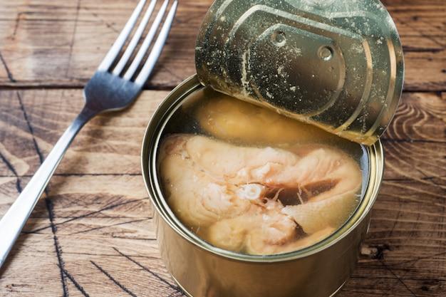 Раскройте жестяную коробку с рыбами розового семг на деревянном столе.
