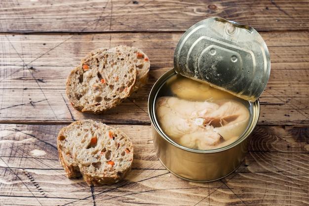 Раскройте консервную банку с рыбами розового лосося и кусками хлеба на деревянном столе.