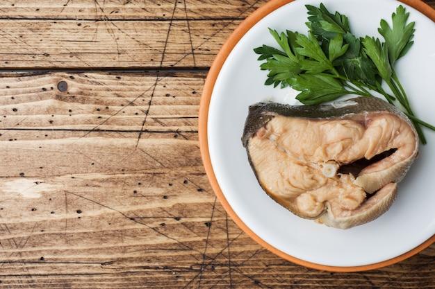 サーモンピンクの魚のスープ、パン、玉ねぎ、ニンニク、木製のテーブルの上の緑の材料。
