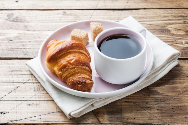 プレートとコーヒー、木製のテーブルの朝食クロワッサン。