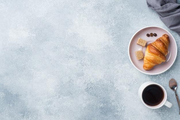 プレート上の朝食のクロワッサンとテーブルの上のコーヒーカップ、