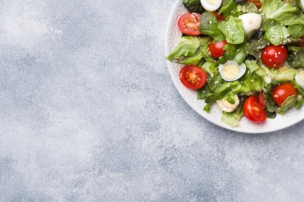 Свежий салат с помидорами и перепелиными яйцами и листьями салата. копировать пространство