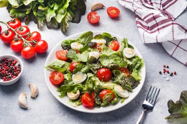 Свежий салат с помидорами и перепелиными яйцами и листьями салата.