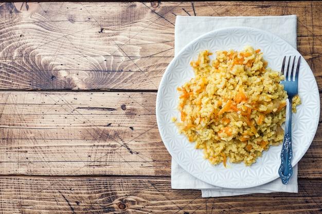 木製のテーブルにご飯と野菜のベジタリアンオリエンタルピラフ。