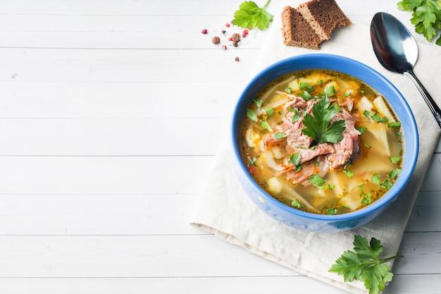 ライトテーブルの上の肉と新鮮なハーブとロシアの伝統的なキャベツスープ。コピースペース