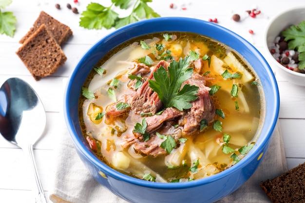 ライトテーブルの上の肉と新鮮なハーブとロシアの伝統的なキャベツスープ。