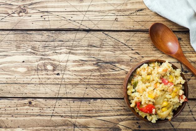 木製の背景に木製のボウルに鶏肉と野菜のピラフ。