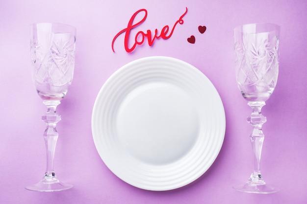 Белая тарелка, два бокала, надпись любви. концепция день святого валентина.