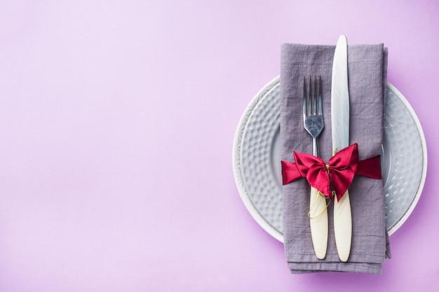 カトラリー、プレートナイフとフォークピンクの背景にナプキンで。休日テーブルのコンセプト