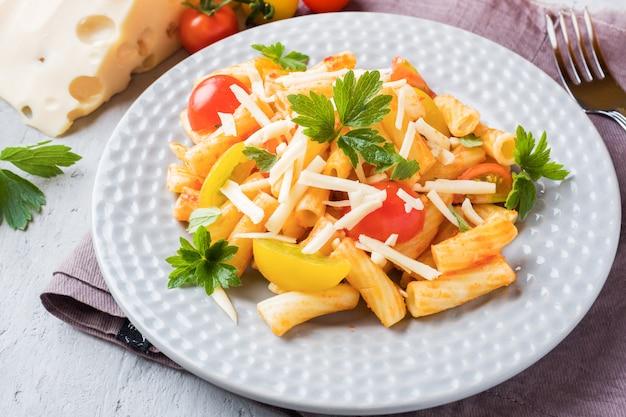 マカロニ、トマトソースのパスタ、木製テーブルの上のプレートのチーズ。
