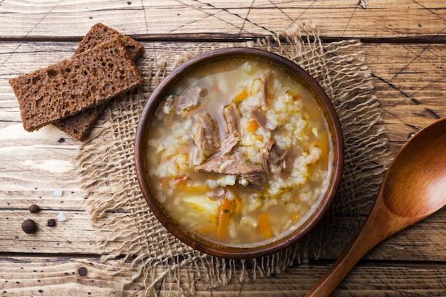 木製のテーブルにご飯と肉のカルチョスープ