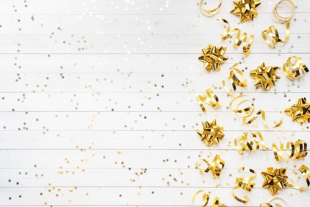 Золотые звезды конфетти и ленты на белом фоне.
