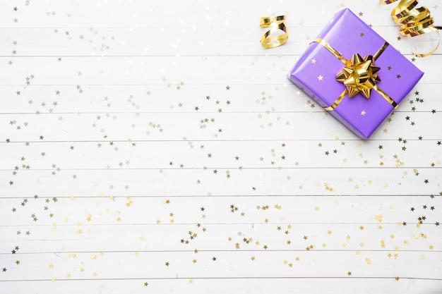 Подарочные коробки с золотыми лентами и бантами, конфетти звезд на белом фоне.