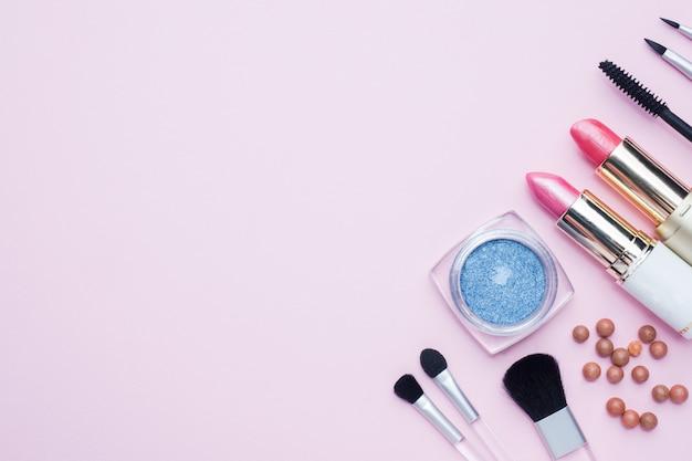 プロの化粧道具。コピースペースとピンクのパステル調の背景に口紅赤面アイシャドウをブラシします。平置き
